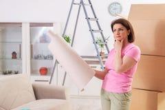 O papel de parede chosing da mulher para a renovação lisa foto de stock royalty free