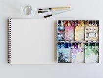 O papel do bloco de desenho da paleta da pintura escova a tabela branca imagem de stock