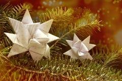 O papel dois protagoniza em um ramo do abeto, bokeh das luzes de Natal no b Imagens de Stock