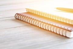 O papel e a pena do caderno na tabela da mesa de escritório com espaço da cópia, aprontam-se adicionando ou zombam-se acima Foto de Stock