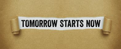 O papel marrom rasgado que revela as palavras começa amanhã agora imagem de stock