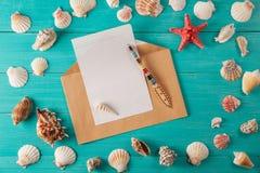 O papel para notas aproxima conchas do mar no fundo de madeira Copie o espaço Fotografia de Stock Royalty Free