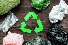 O papel recicla o sinal com lixo plástico na opinião superior do fundo de madeira Imagem de Stock