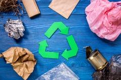 O papel recicla o sinal com lixo plástico na opinião superior do fundo de madeira azul Imagem de Stock Royalty Free