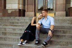 O par é de sorriso e de assento nas etapas, abraçar, datando Amor imagens de stock