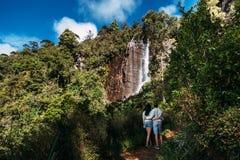 O par admira uma cachoeira bonita fotografia de stock