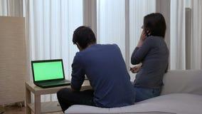 O par adulto que senta-se na borda da cama com um portátil e um homem ansioso discute no telefone video estoque