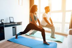 O par afro-americano que faz a ioga exercita em casa Estão no assoalho em esteiras da ioga imagens de stock royalty free