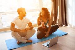 O par afro-americano que faz a ioga exercita em casa Sentam-se no assoalho em esteiras da ioga em uma posição de lótus fotos de stock