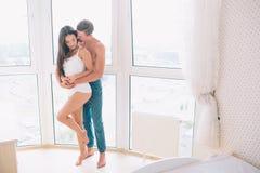 O par agradável está estando junto na janela Abraça-a Guarda suas mãos no seu O indivíduo está beijando a menina Olha fotografia de stock