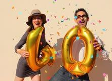 O par alegre comemora um aniversário de quarenta anos com os balões dourados grandes e pedaços de papel pequenos coloridos no ar Foto de Stock