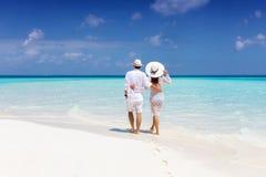 O par anda ao longo de uma praia tropical em Maldivas imagem de stock