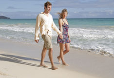 O par anda nas mãos da terra arrendada da praia Imagens de Stock