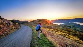 O par aprecia o cenário bonito de Akaroa perto de Christchurch em Nova Zelândia O par romântico vai na viagem por estrada fotografia de stock
