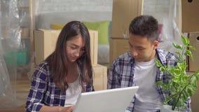 O par asiático novo conduz em um apartamento novo, sentando-se no assoalho e usando um fim do portátil acima video estoque