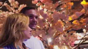O par bonito de amantes está estando na alameda entre o cenário, sakura de florescência video estoque