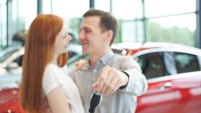 O par bonito está guardando a chave de seu carro novo, olhando a câmera e o sorriso filme