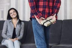O par bonito feliz junto em casa, um homem dá a uma mulher um g Fotos de Stock