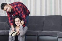 O par bonito feliz junto em casa, um homem dá a uma mulher um g Imagem de Stock Royalty Free