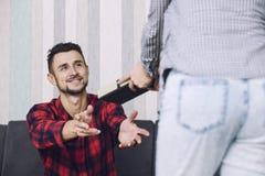 O par bonito feliz, uma mulher dá a um homem um presente para o holid Fotos de Stock
