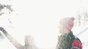 O par bonito novo, menina joga a neve, na floresta do inverno em um dia ensolarado, alargamento da luz solar video estoque
