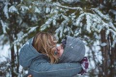 O par coberto de neve feliz que beija sob o abeto ramifica em feriados românticos saudáveis do conceito da floresta do inverno no Fotografia de Stock Royalty Free