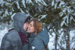 O par coberto de neve feliz que beija sob o abeto ramifica em feriados românticos saudáveis do conceito da floresta do inverno no Fotos de Stock Royalty Free