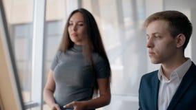 O par criativo novo do negócio está trabalhando no projeto que está no interior do escritório vídeos de arquivo