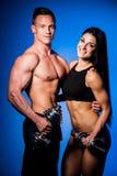 O par da aptidão levanta no estúdio - homem e mulher aptos Imagem de Stock Royalty Free