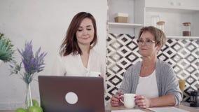 O par da família de mulher e de neta superiores é de assento e de fala pela conferência em linha do portátil video estoque