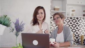 O par da família da mulher dois é de assento e de riso ao beber o chá saboroso vídeos de arquivo