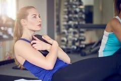O par de mulheres adultas novas que fazem o músculo abdominal exercita fotos de stock