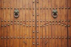 O par de puxador dá forma como dois leões em uma porta de madeira Fotografia de Stock