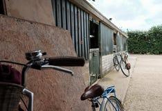 O par de seu e do seu bicycles considerado inclinado contra uma parede em uma jarda da libré do cavalo imagens de stock royalty free