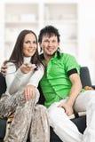 O par de sorriso presta atenção à tevê Foto de Stock