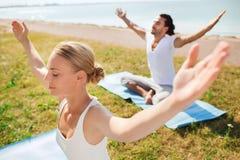 O par de sorriso que faz a ioga exercita fora Imagens de Stock Royalty Free
