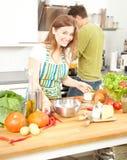 O par desportivo feliz está preparando o alimento saudável na cozinha clara fotografia de stock