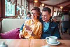 O par do amor olha no álbum de fotografias do telefone fotografia de stock