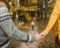 O par dos povos da família que guarda a criança da mão corre imagem de stock royalty free