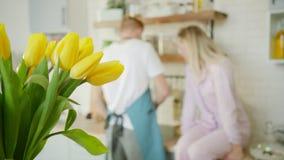 O par está beijando na cozinha ao cozinhar no fundo fora de foco video estoque