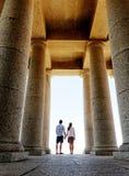 O par está em um momument com grandes colunas foto de stock