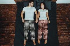 O par está encontrando-se na cama e está guardando-se as mãos imagem de stock