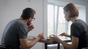 O par está sentando-se na tabela no tempo de manhã na cozinha de seu apartamento e está comendo-se a omeleta, usando a faca e a f video estoque