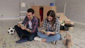 O par está sentando-se no apartamento e está contando-se o dinheiro video estoque