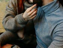 O par está sentando-se no assoalho em um abraço embrace uma mão fêmea com um anel estica para tocar na cara de um homem beijo Ta fotografia de stock royalty free