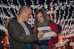O par feliz abre junto a caixa com um presente imagens de stock