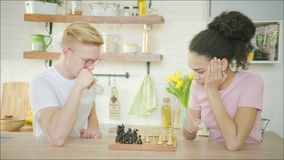 O par feliz caucasiano e afro-americano está jogando a xadrez junto filme
