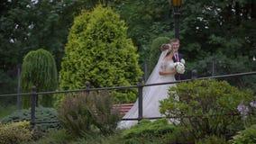 O par feliz do recém-casado no amor é ing da conversa e passeio ao longo do jardim de florescência bonito filme