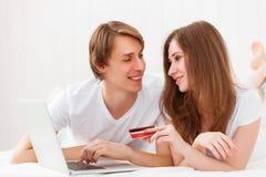 O par feliz faz a compra em linha com portátil e cartão de crédito a foto de stock