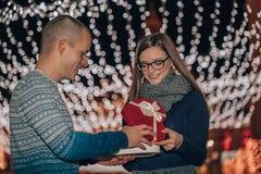 O par feliz novo abre junto a caixa com um presente imagem de stock